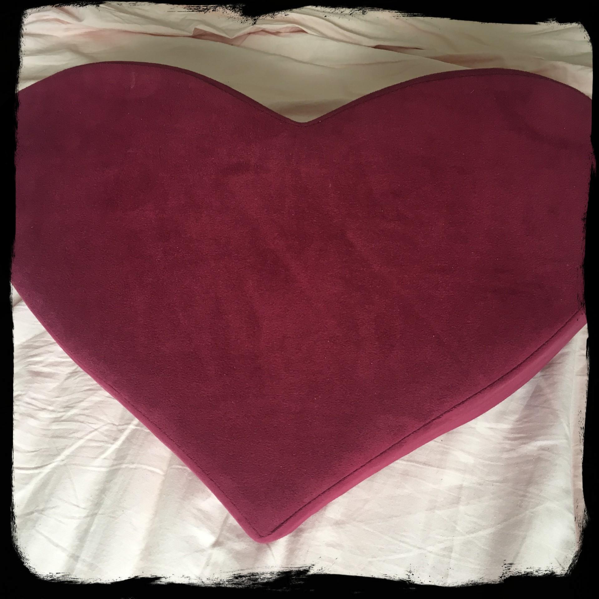 Het Heart Wedge kussen op een bed.