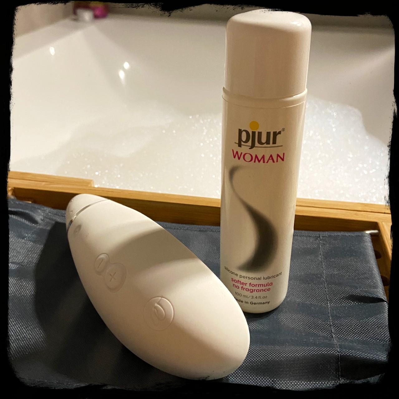 De Womanizer Premium en het Woman glijmiddel van Pjur met badschuim in de achtergrond.